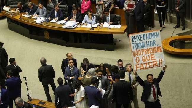 """Deputado ergue cartaz com os dizeres """"deixe o homem trabalhar"""""""