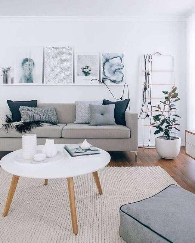 9. Decoração estilo escandinavo em sala com sofá cinza.