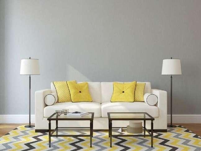 32. Sala com parede cinza almofadas amarelas e tapete geométrico