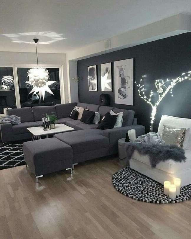 35. Sala com parede preta e sofá cinza