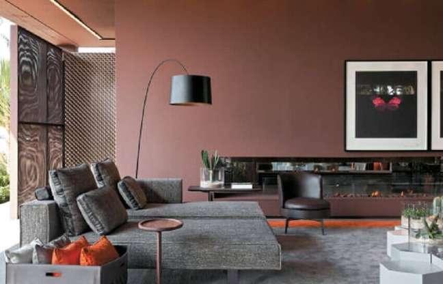 29. Sala com sofá cinza e parede rose com luminária moderna