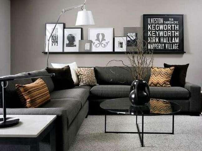 28. Sala preta e cinza com quadros na prateleira