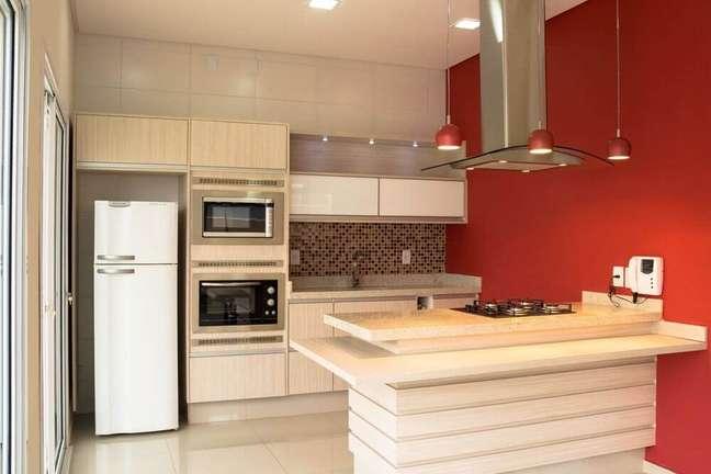 24. Decoração de cozinha com coifa de ilha em vidro e alumínio e com pendentes vermelhos