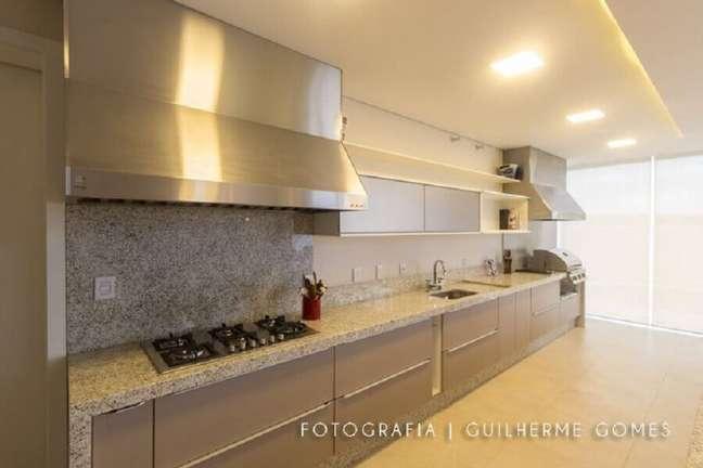 38. Decoração de cozinha planejada com coifa de parede e cores neutras