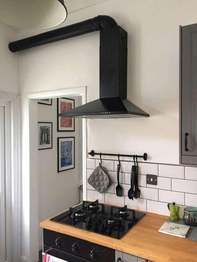 12. Decoração no estilo minimalista em cozinha com coifa de parede preta.