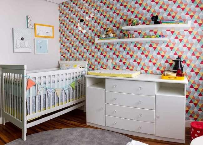 18. Quarto de bebê com papel de parede estampado com triângulos coloridos