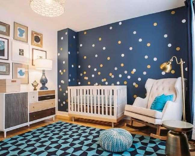 2. Modelo de papel de parede para quarto de bebê com bolinhas douradas e brancas e fundo azul marinho.