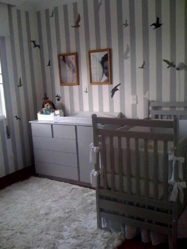 24. Quarto de bebê com decoração em tons de cinza e com papel de parede listrado com desenhos de pássaros
