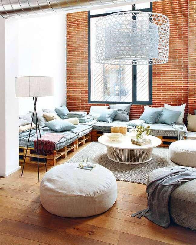 14. Sala com estilo moderno e sofá de palete com tons claros de azul e cinza