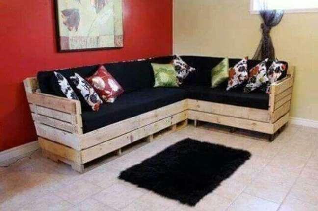 74. Sofá em L com almofadas pretas e estampadas
