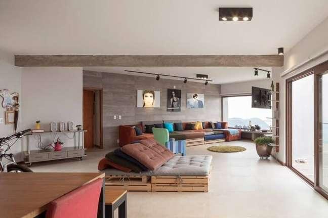 68. Sofá de paletes entre salas integradas. Projeto de Marlette Lim