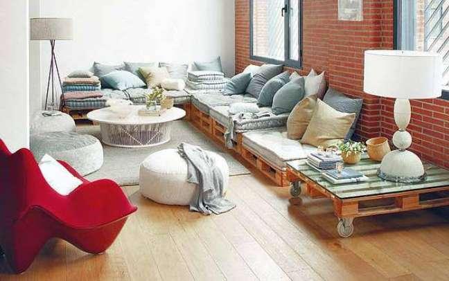 40. Sofá de pallets em L com uma mesa de apoio de pallets também
