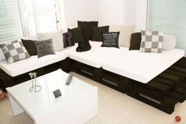 39. Sofá de palete preto é uma forma bem moderna e barata para mudar o ambiente