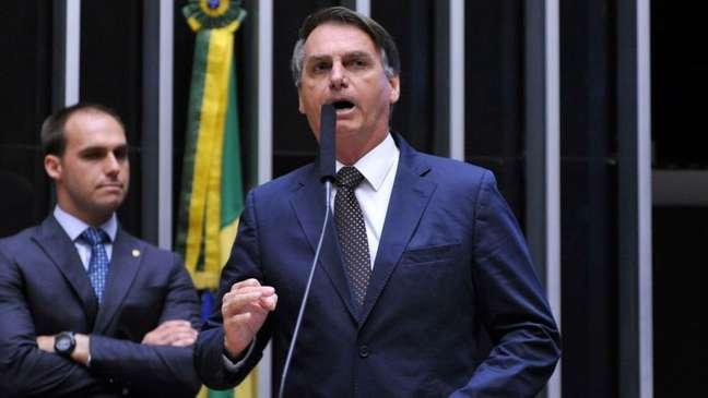 Jair Bolsonaro (à frente, à dir.) e seu filho Eduardo Bolsonaro (à esq., atrás), no plenário da Câmara