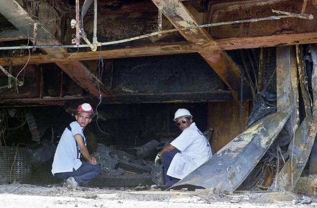 Técnicos trabalham nos escombros deixados pela explosão que matou 21 pessoas em 2003