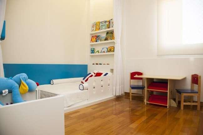 35. A cama branca dá um destaque legal com o chão de madeira e as cores mais fortes dos brinquedos e demais móveis. Projeto de Tikkanen Arquitetura