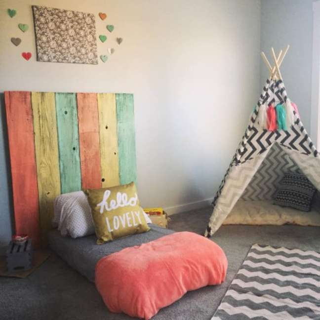 68. O charme está nos detalhes: as cores usadas na cabeceira são as mesmas dos corações na parede e das franjas na cabana montessoriana