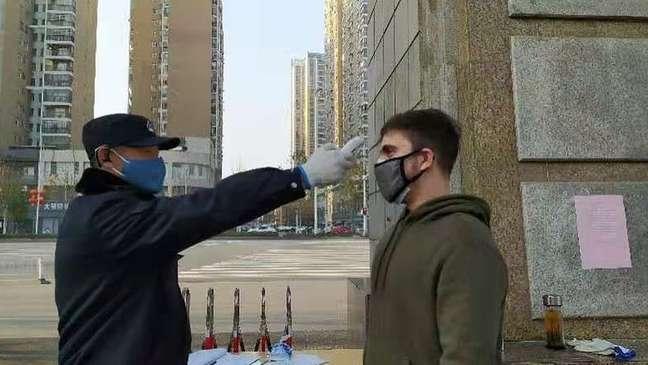 Alefy passando por teste para medir sua temperatura em Wuhan, para verificar se não estava com febre