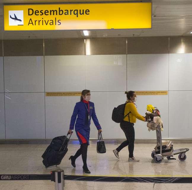 Passageira e tripulante desembarcam usando máscara no Terminal 3 do Aeroporto internacional de Guarulhos, na Grande São Paulo, em meio à epidemia do novo coronavírus.