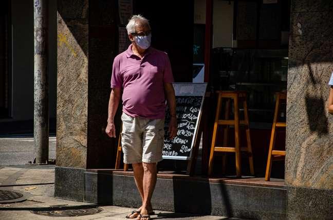 Pedestres são vistos usando máscara de proteção facial pelas ruas do bairro de Botafogo, na zona sul do Rio de Janeiro