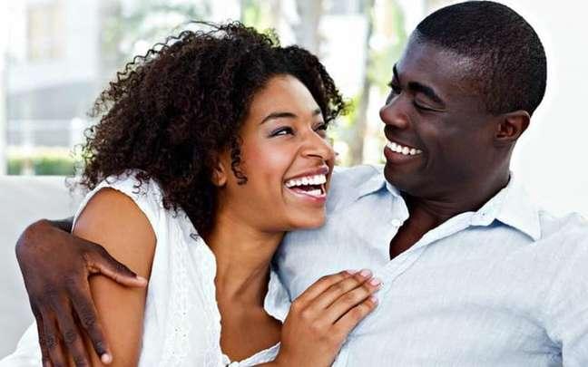 Mulher e homem se abraçando sentados, ambos riem