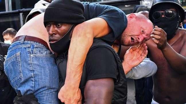 Foto de Patrick Hutchinson carregando um manifestante viralizou nas redes sociais