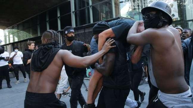 Os amigos de Hutchinson tiveram que protegê-lo enquanto carregava manifestante para que eles não fossem agredidos