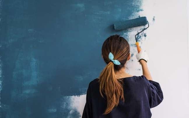 Mulher de costas pintando uma parede de azul