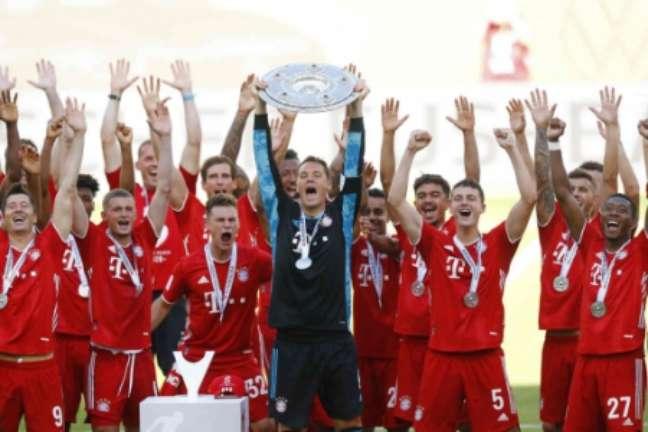 Neuer erguendo a taça de campeão (Foto: KAI PFAFFENBACH / AFP)