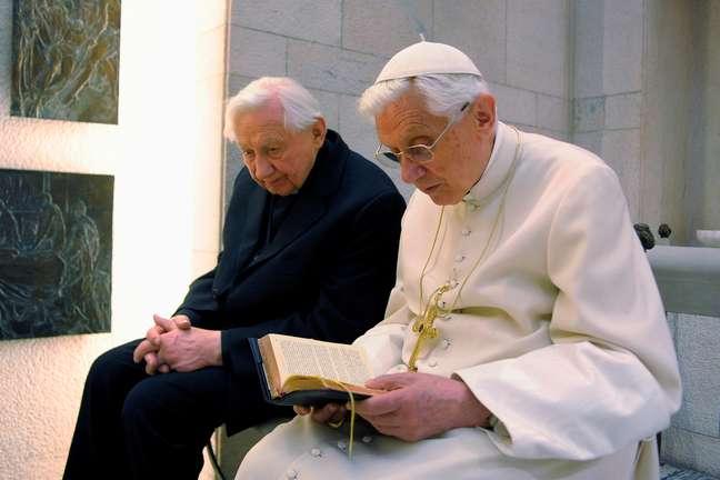 Ex-papa Bento 16 ora ao lado de seu irmão, Georg Ratzinger, em capela particular 14/04/2012  REUTERS/Osservatore Romano/