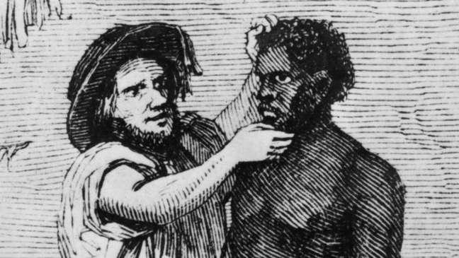 Comerciantes brancos inspecionam escravos africanos durante uma venda, por volta de 1850