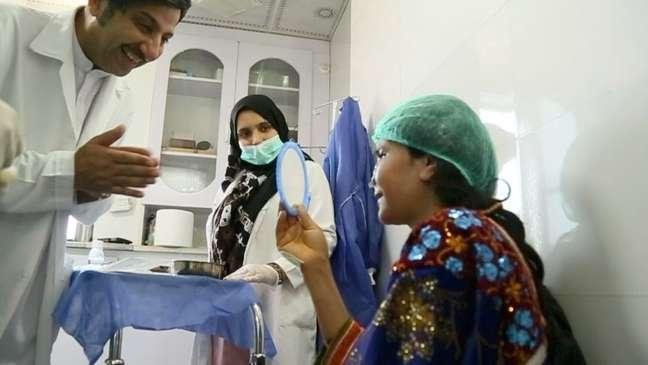Zarka se olha em um espelho de mão após a cirurgia