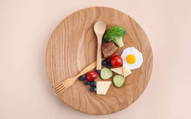 Prato de comida com talheres imitando ponteiros de um relógio e comidas em uma parcela dele