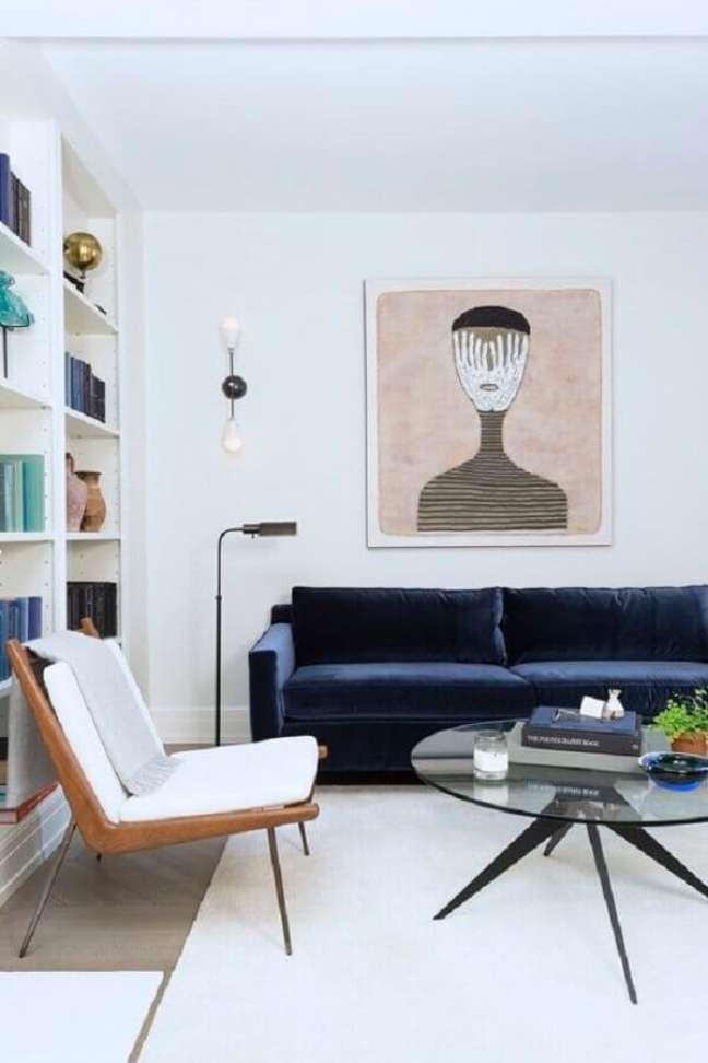 51. Sala branca decorada com estante de nichos, sofá azul de veludo e poltrona decorativa de madeira moderna – Foto: Simplichique