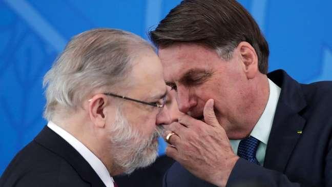 O presidente Jair Bolsonaro cobre a boca e fala algo no ouvido do PGR Augusto Aras