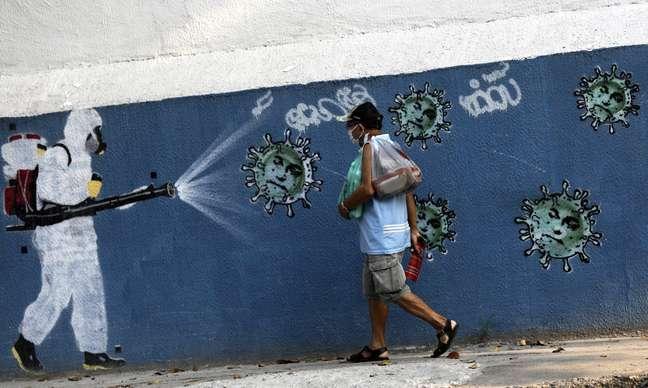 Homem passa por grafite sobre Covid-19 no Rio de Janeiro 07/10/2020 REUTERS/Ricardo Moraes