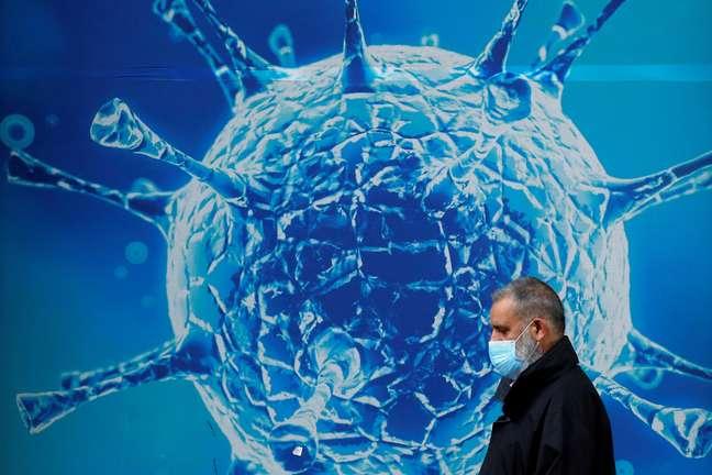 Homem usando máscara passa em frente a ilustração de vírus em Oldham, no Reino Unido 03/08/2020 REUTERS/Phil Noble