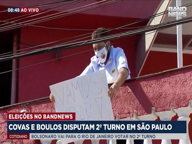 Boulos segura cartaz na sacada da sua casa