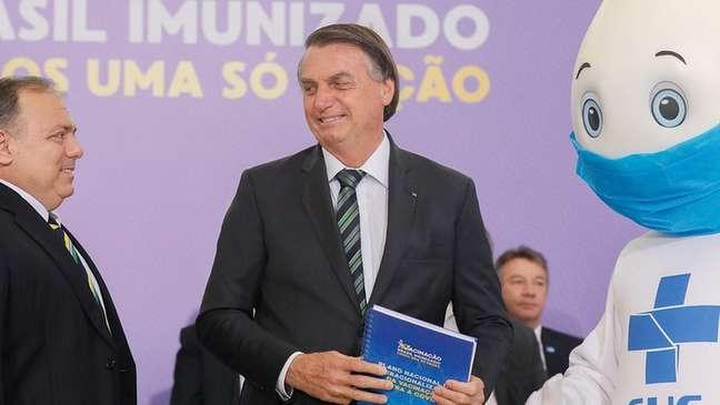 Bolsonaro (ao centro) recebe do ministro da Saúde, Eduardo Pazuello (à esquerda), e do personagem Zé Gotinha (à direita) o Plano Nacional de Operacionalização da Vacinação contra a covid-19 em evento no dia 16 de dezembro de 2020