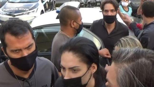 Dr Jairinho (saindo do carro) e Monique (à frente na foto), presos nesta quinta, estão sendo acusados de atrapalhar as investigações sobre a morte do filho dela