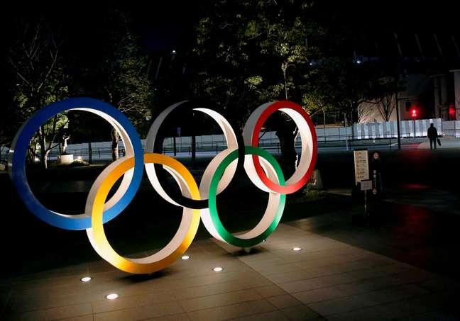 Os anéis olímpicos são iluminados em frente ao Estádio Nacional de Tóquio, no Japão
