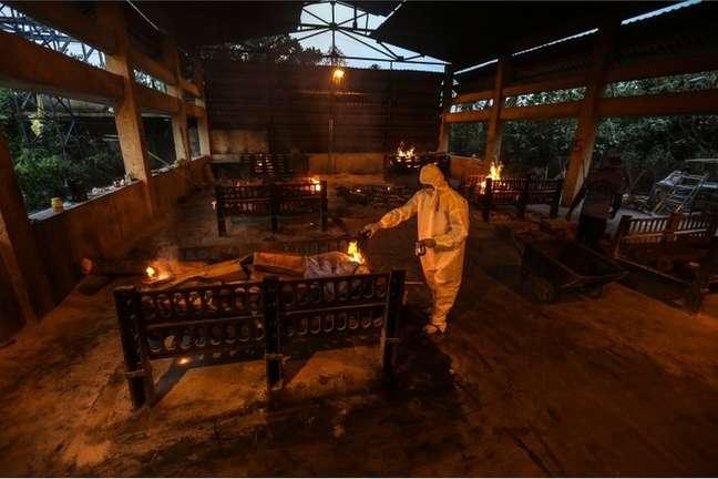 Parentes e funcionários municipais realizam os últimos ritos para as vítimas da covid-19 em local de cremação em Mumbai