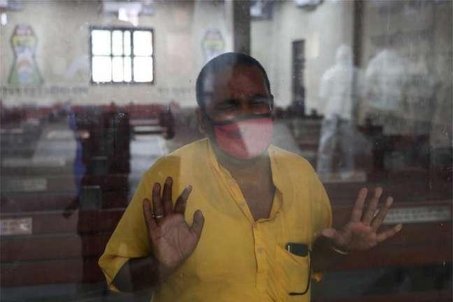 Em um crematório em Delhi, homem aguarda cremação de membro da família que morreu de coronavírus