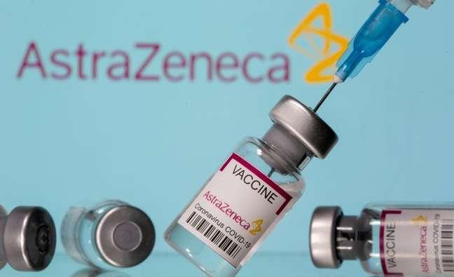 Frascos rotulados como de vacina da AstraZeneca contra Covid-19 em frente ao logo da empresa em foto de ilustração 14/03/2021 REUTERS/Dado Ruvic