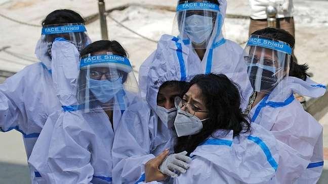 Grupo de trabalhadoras da saúde com equipamento de proteção individual se abraça
