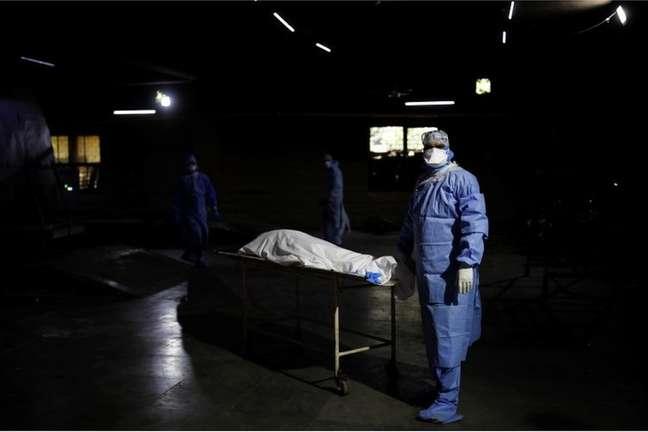 Espera para cremação em Delhi: profissional de saúde ao lado do corpo de um homem que morreu de covid-19