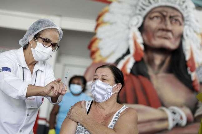 Profissional de saúde mostra seringa para paciente depois de aplicar vacina contra Covid-19 CoronaVac no Rio de Janeiro 08/04/2021 REUTERS/Ricardo Moraes