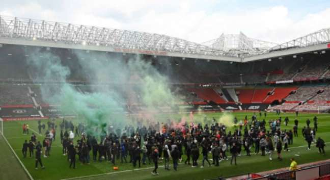 Torcedores do Manchester United invadiram o gramado de Old Trafford (Foto: OLI SCARFF / AFP)