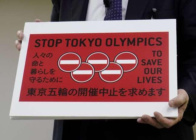 Advogado Kenji Utsunomiya exibe cartaz durante entrevista coletiva em Tóquio após envio de petição solicitando o cancelamento da Olimpíada de Tóquio, no Japão 14/05/2021 REUTERS/Naoki Ogura
