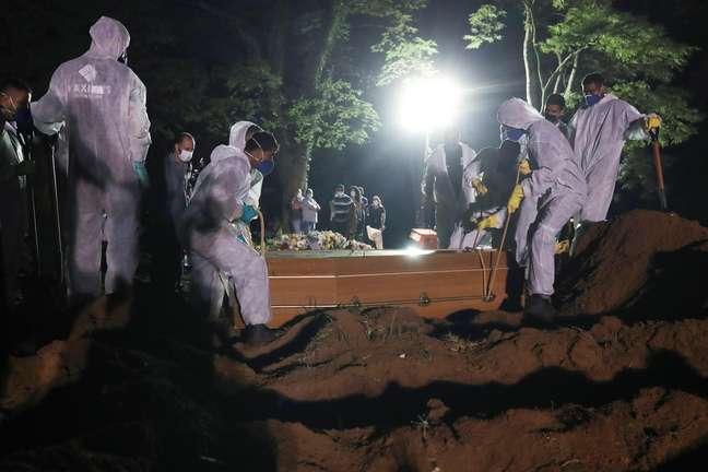 Coveiros com trajes de proteção fazem o sepultamento noturno no cemitério de Vila Formosa, em São Paulo